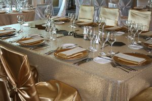 Wedding head table: Champagne sequin tablecloth and champagne universal satin chair covers