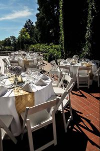 Wedding party guest tables: White polyester tablecloths and napkins with champagne pintuck runners