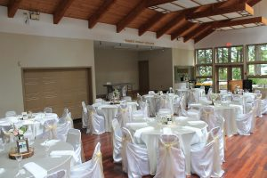 Wedding guest tables: Ivory satin tablecloths and white universal satin chair covers with champagne organza sashes