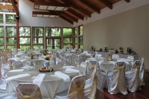 Wedding guest tables: Ivory satin tablecloths with white polyester napkins and white universal satin chair covers with champagne organza sashes