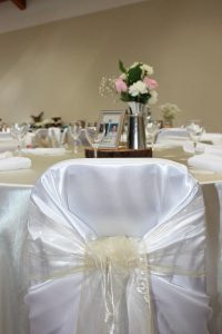 Wedding guest chairs: White universal satin chair covers with champagne organza sashes